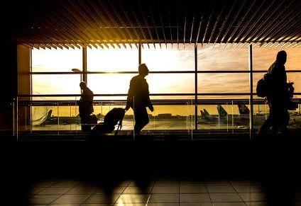Persona che cammina in aeroporto al tramonto