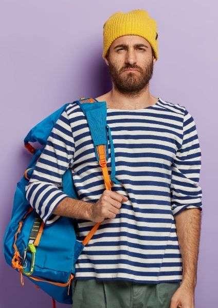 ragazzo confuso su come indossare uno zaino da viaggio