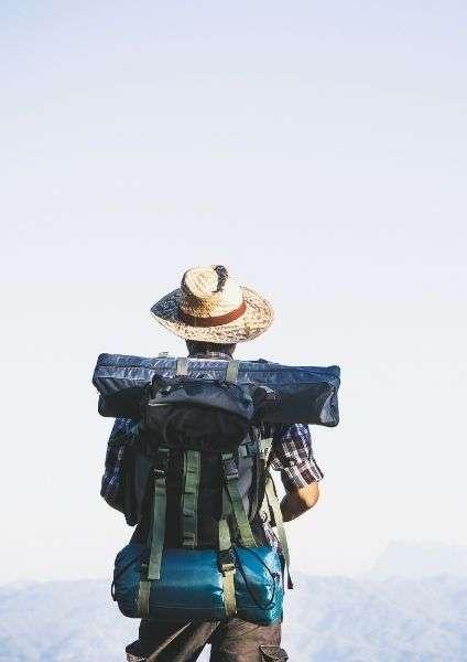 viaggiatore di schiena con zaino in spalla