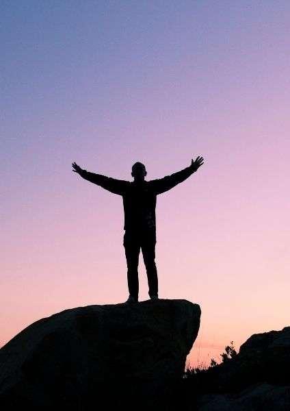 Uomo al tramonto su una roccia a braccia spalancate