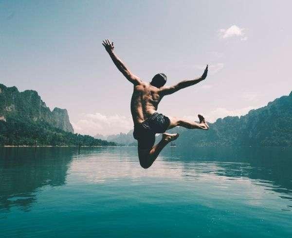ragazzo che salta davanti a un lago