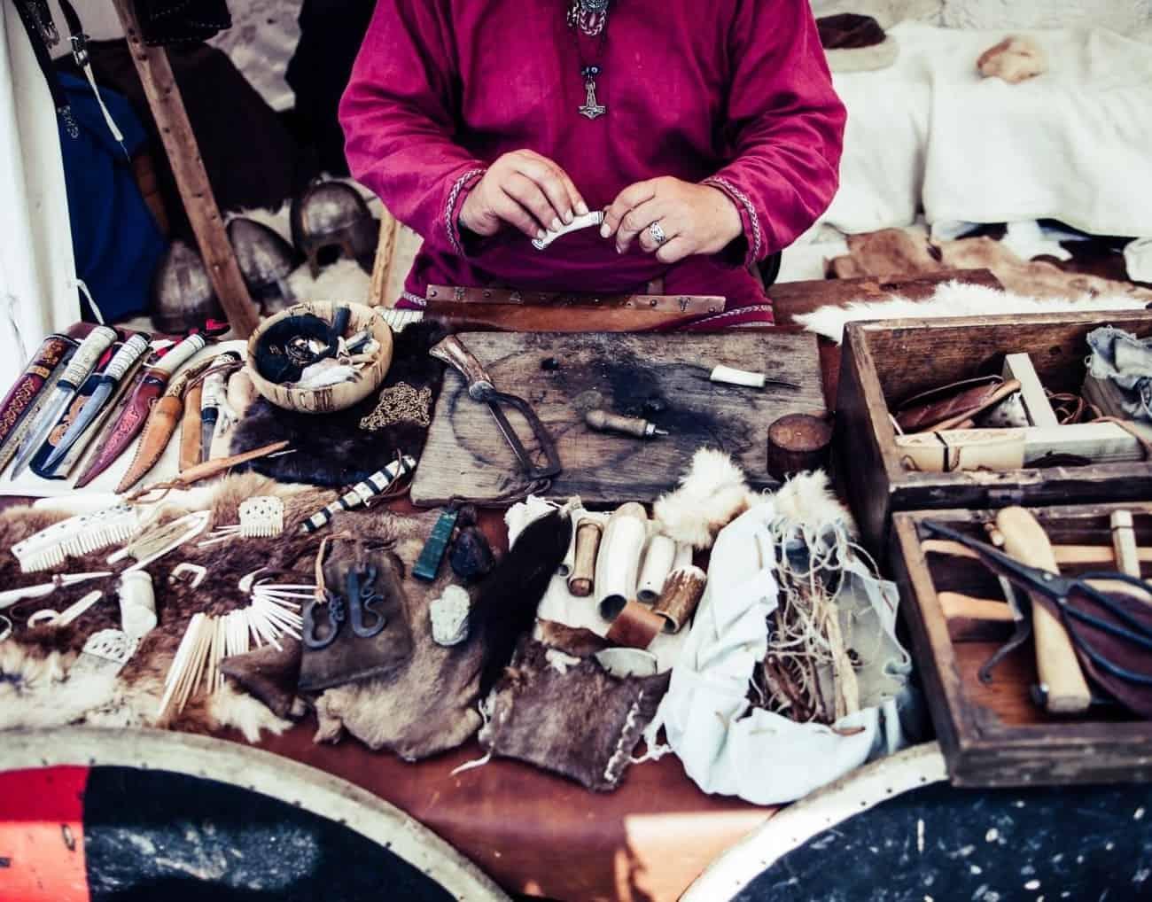 primo piano su un tavolo da lavoro con lavori artigianali e mani che lavorano sullo sfondo