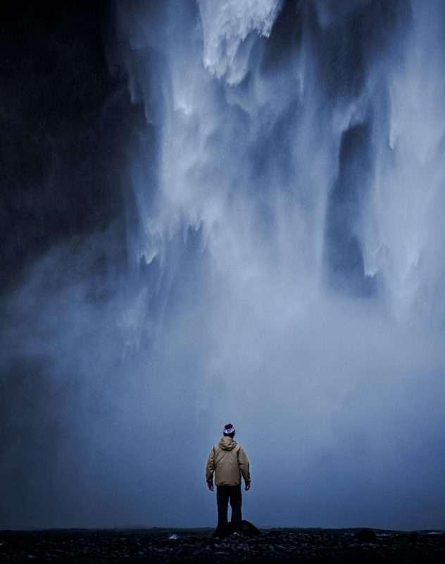 Uomo vicino ad una cascata impetuosa
