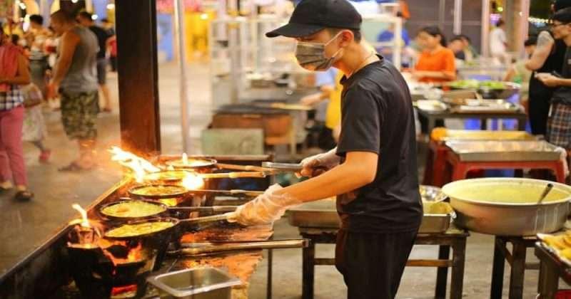 uomo che cucina in uno street food
