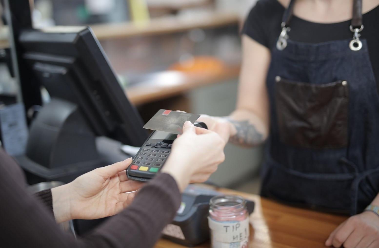 primo piano di mani di un cliente che paga con carta di credito in un negozio
