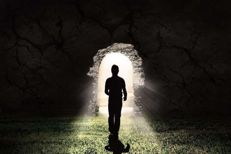 uomo nell'ombra che cammina verso una porta piena di luce