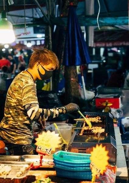 uomo che cucina in sicurezza in uno street food