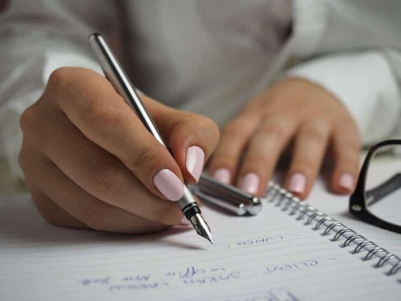 Mani di ragazza che scrivono su un quaderno