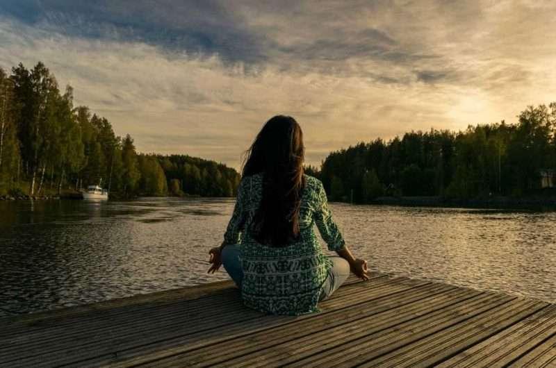 ragazza che medita a riva di un lago