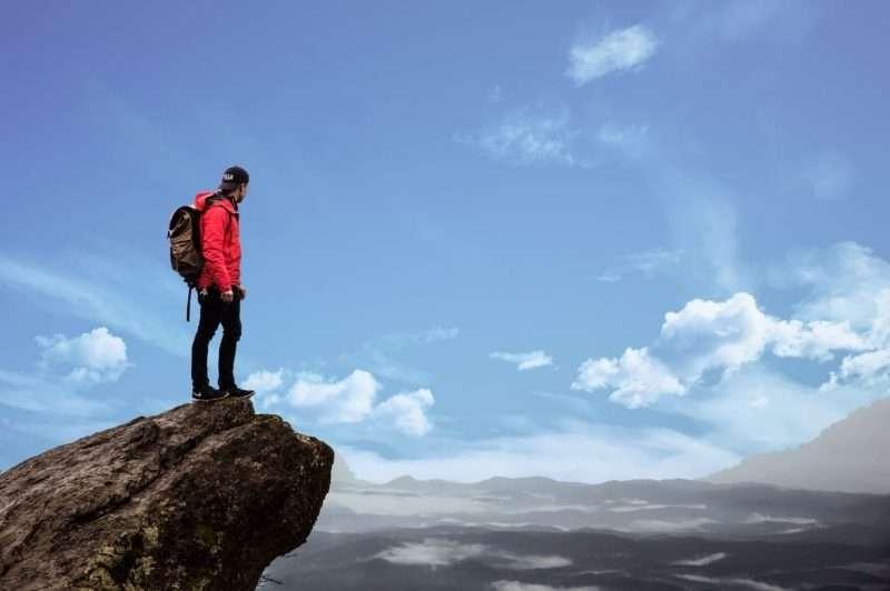uomo sul picco di una montagna che riesce ad inseguire i proprio sogni