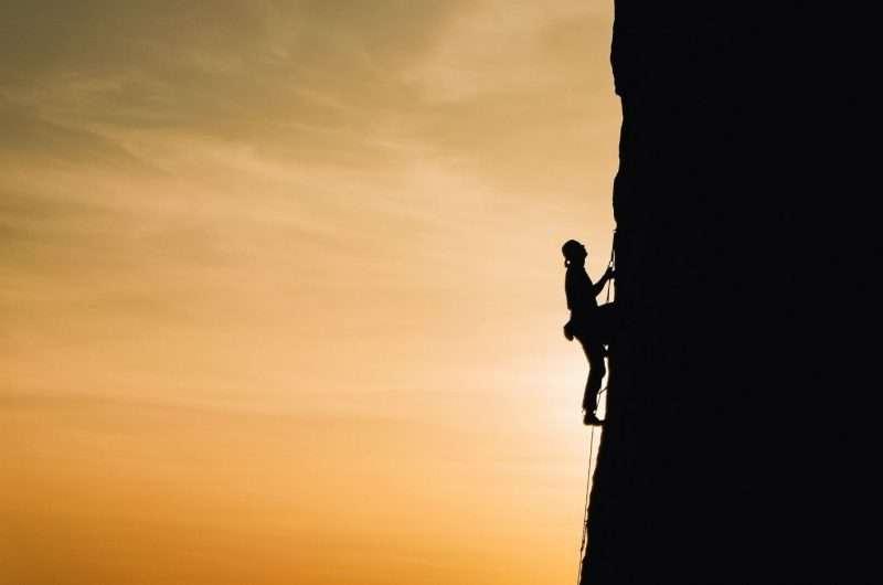 persona che scala un grande pendio al tramonto per inseguire i proprio sogni