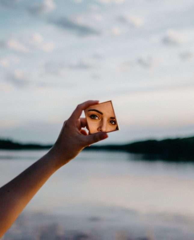 Volto di ragazza che si riflette su un piccolo specchio su di uno sfondo lacustre
