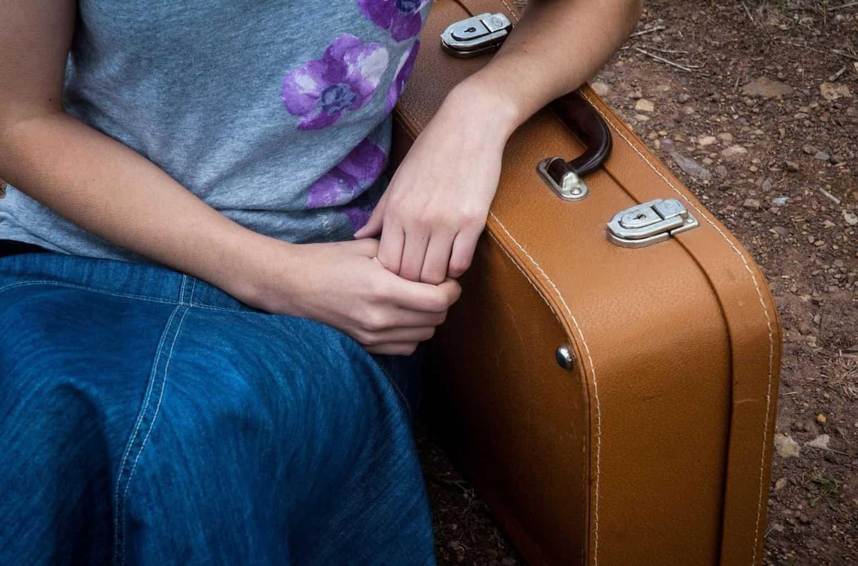 Primo piano sulle mani di una donna poggiata su una valigia