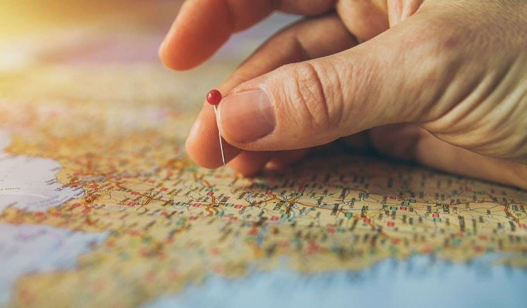 Mano su una carta geografica che scegli una destinazione con una puntina