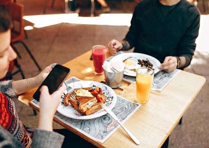 ragazze al tavolo con cibo pronto da mangiare, una delle ragazze fotografa cibo