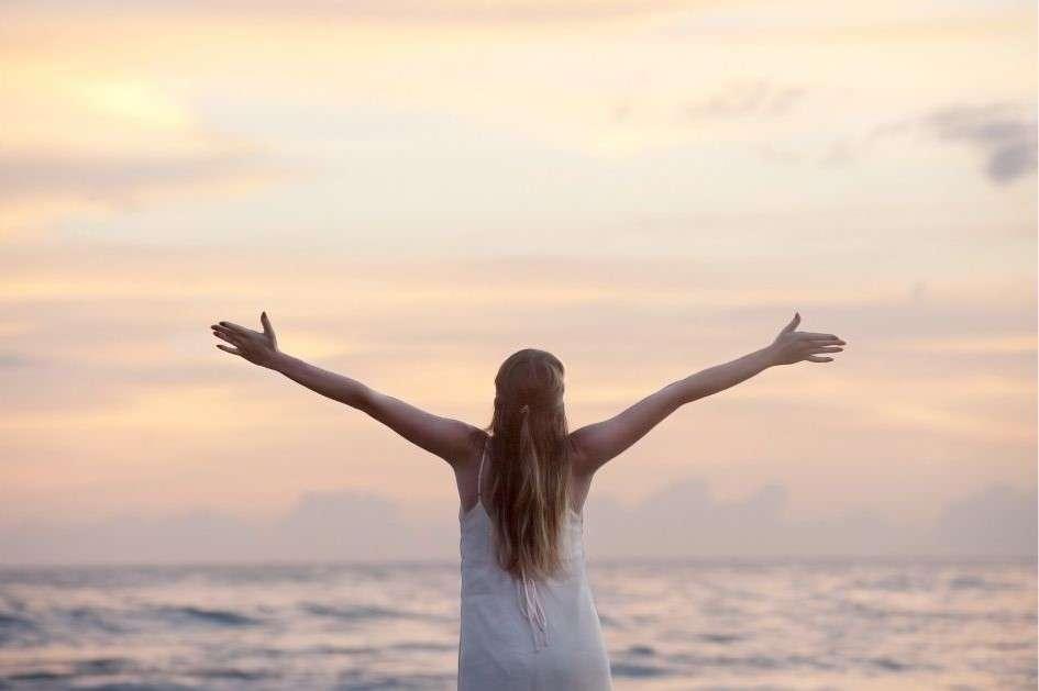 ragazza di spalle con braccia spalancate con sfondo tramonto al mare