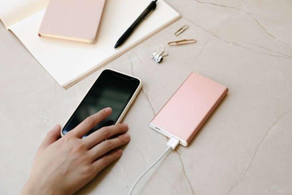 smartphone collegato ad un powerbank con penne e taquino