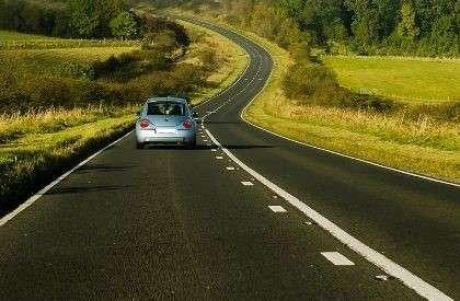 automobile che scorre lungo una strada con curve in una campagna verde - come lasciare i tuoi beni