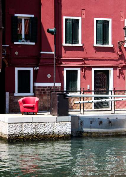 Cosa vedere a Chioggia: le serate sono animate dalle chiacchere seduti in calle. Nell'immagine: una poltrona rossa posta di fronte ad una tipica casa rossa con scuri verdi.