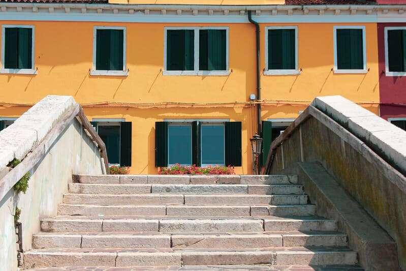 Cosa vedere a Chioggia: i ponti sono numerosi, in foto si gioca con la prospettiva e il ponte risulta alto come la finestra del secondo piano di una casa le chiacchere seduti in calle. Nell'immagine: una poltrona rossa posta di fronte ad una tipica casa rossa con scuri verdi.