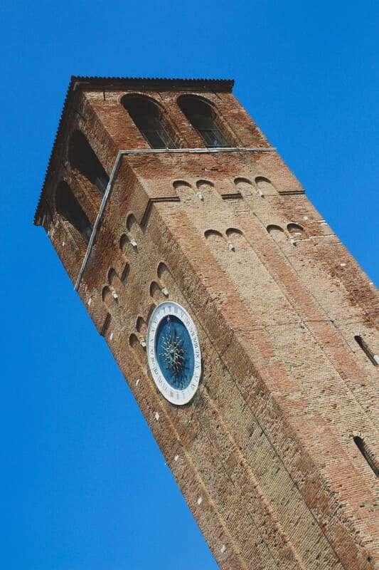 Cosa fare e cosa vedere a Chioggia: la torre dell'orologio più antico al mondo su cielo azzurro