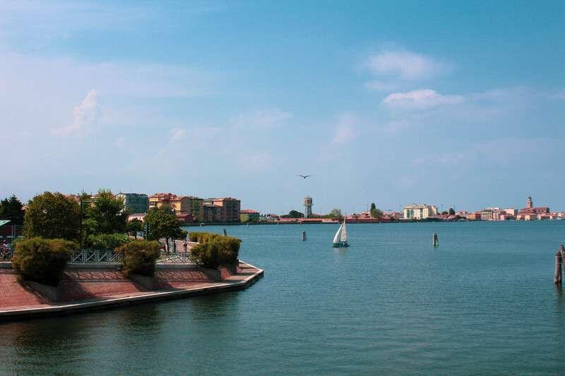 Cosa fare e cosa vedere a Chioggia: una barca a vela naviga la laguna del Lusenzo. Sulla riva si vedono le piante di tamerici non in fiore