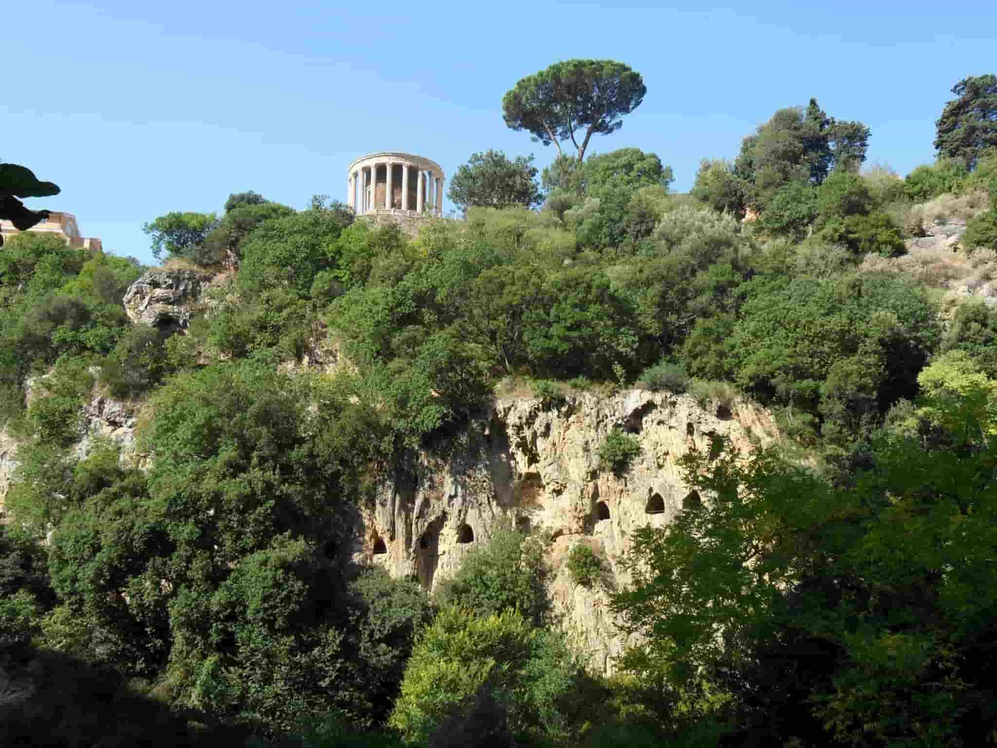 Collina con alberi; in cima il Tempio romano di vesta. Sotto tunnel scavati nella roccia. Villa Greogoriana